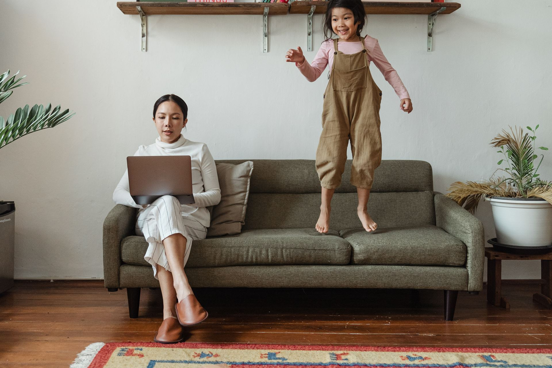 a woman sits on a couch with her laptop on her legs while a young child jumps on the couch next to her; plants are visible on either side of the couch